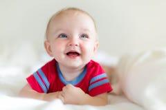 Bebê adorável feliz que ri e que joga na cama branca macia imagem de stock