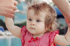 Bebê adorável que guarda as mãos do pai ao aprender andar fora Fundo da piscina Bebê que olha acima imagens de stock