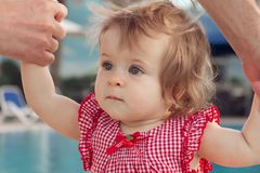 Bebê adorável que guarda as mãos do pai ao aprender andar fora Fundo da piscina Bebê que olha acima imagem de stock