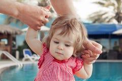 Bebê adorável que guarda as mãos do pai ao aprender andar fora Fundo da piscina Bebê que olha para baixo fotografia de stock