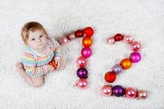 Bebê adorável que guarda a bola colorida do brinquedo do xmas do vintage nas mãos bonitos Criança pequena e de árvore de Natal bo Imagem de Stock Royalty Free