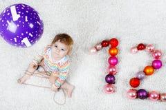 Bebê adorável que guarda a bola colorida do brinquedo do xmas do vintage nas mãos bonitos Criança pequena e de árvore de Natal bo Imagens de Stock