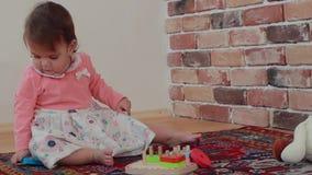 Bebê adorável que senta-se no assoalho e que joga o brinquedo em casa, vídeo de movimento lento filme