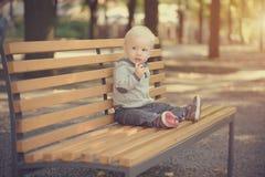 Bebê adorável que senta-se no banco Fotografia de Stock