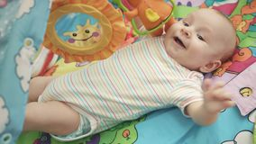 Bebê alegre que encontra-se na esteira colorida Infante feliz que joga na esteira tornando-se video estoque