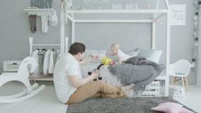 Bebê alegre que joga brinquedos com paizinho amado em casa video estoque