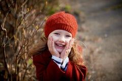 Bebê 3 anos com cabelo longo Em suportes de uma boina vermelha e do revestimento na rua na luz do sol, guardando o punho do Imagens de Stock
