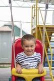 Bebê 2 anos que montam em um balanço Criança feliz no campo de jogos foto ertical imagem de stock