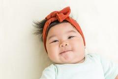 Bebê asiático adorável que sorri na cama Fotos de Stock