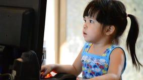Bebê asiático bonito que joga o computador