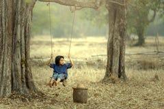 Bebê asiático no balanço, Sakonnakhon, Tailândia imagem de stock