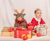 Bebê asiático no terno de Papai Noel Foto de Stock
