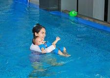 Bebê asiático novo do ensino da mamã na piscina fotos de stock