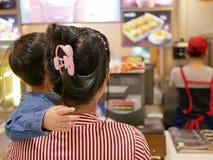 Bebê asiático pequeno junto com sua mãe que olha fotos do alimento e que lê o menu na parede do restaurante para decidir que à or imagens de stock royalty free