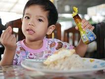 Bebê asiático pequeno que aprende decidir só em quanto molho do feijão da soja deve ser adicionado em seu ovo frito imagem de stock