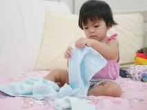 Bebê asiático pequeno que aprende dobrar a roupa fotografia de stock