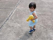 Bebê asiático pequeno que guarda sua boneca favorita ao aprender andar só imagem de stock