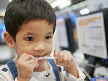 Bebê asiático pequeno que toma uma palha para fora de seu pacote usando seus dentes foto de stock royalty free