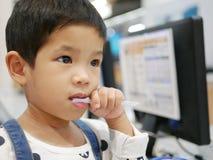 Bebê asiático pequeno que toma uma palha para fora de seu pacote usando seus dentes fotografia de stock
