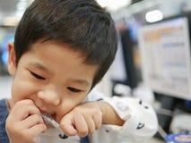 Bebê asiático pequeno que toma uma palha para fora de seu pacote usando seus dentes fotos de stock