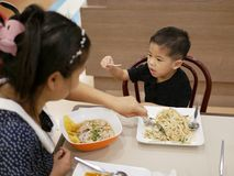 Bebê asiático que pegara um beansprout de seu alimento e que negocia com a mamã para não o comer imagens de stock royalty free