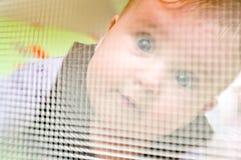 Bebê atrás do engranzamento do playpen fotografia de stock