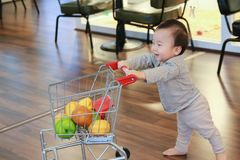 Bebê bonito asiático que empurra o brinquedo de compra do trole foto de stock royalty free