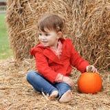 Bebê bonito com abóboras em uma exploração agrícola Fotos de Stock