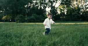Bebê bonito com a camisa do wite que corre no campo de grama Movimento lento 4K vídeos de arquivo