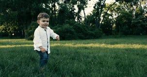 Bebê bonito com a camisa do wite que corre no campo de grama Movimento lento 4K Epopeia vermelha Por do sol filme