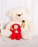 Bebê bonito com o urso de peluche grande na sala branca Imagens de Stock Royalty Free
