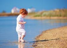 Bebê bonito da criança do ruivo que anda na água na costa do lago do verão Imagens de Stock
