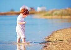 Bebê bonito da criança do ruivo que anda na água na costa do lago do verão Foto de Stock Royalty Free
