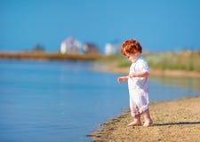 Bebê bonito da criança do ruivo que anda na costa do lago na manhã do verão Fotografia de Stock