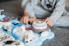 Bebê bonito da criança que joga com placa ocupada em casa imagens de stock royalty free