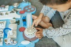 Bebê bonito da criança que joga com placa ocupada em casa foto de stock royalty free