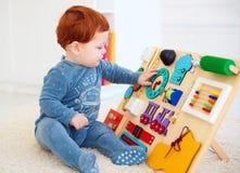 Bebê bonito da criança que joga com placa ocupada em casa foto de stock
