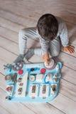Bebê bonito da criança que joga com placa ocupada em casa imagem de stock royalty free