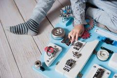 Bebê bonito da criança que joga com placa ocupada em casa fotografia de stock royalty free