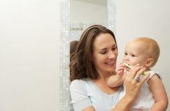 A bebê bonito de sorriso da mãe ensinando como escovar os dentes com escova de dentes fotografia de stock