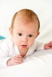 Bebê bonito do bebê que encontra-se na cama em sua barriga fotos de stock