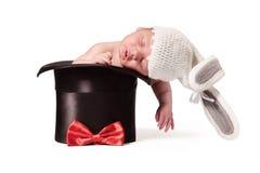 Bebê bonito doce no chapéu feito malha com as orelhas de coelho no chapéu de seda no fundo branco Fotografia de Stock Royalty Free
