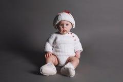 Bebê bonito em um vestido e em um tampão da malha imagem de stock royalty free