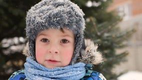 Bebê bonito na roupa e em vestir do inverno um chapéu na perspectiva da neve e de uma árvore de Natal vídeos de arquivo