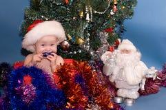 Bebê bonito no chapéu vermelho na frente da árvore de Natal fotografia de stock