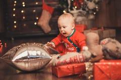 Bebê bonito no traje de Santa Claus para o Natal que joga a sagacidade Foto de Stock