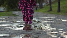 Bebê bonito nos macacões cor-de-rosa mornos que correm através das poças video estoque