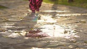 Bebê bonito nos macacões cor-de-rosa mornos que correm através das poças filme