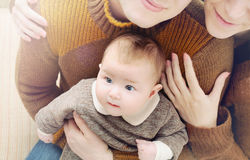 Bebê bonito pequeno com os olhos grandes que sentam-se nos joelhos do pai, fá foto de stock royalty free