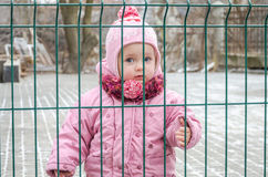 Bebê bonito pequeno da menina atrás da cerca, da grade fechado em um tampão e de um revestimento com emoção triste em sua cara Fotografia de Stock Royalty Free